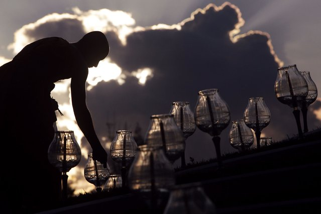 """A Buddhist monk prepares candles for the main event of the Yee Peng festival at a temple in the northern capital of Chiang Mai October 25, 2014. The annual festival is celebrated as a religious event in which locals throughout the region make merit and carry out other religious activities. The highlight of the event is the launching of the """"Khom loy"""" or floating lanterns into the night sky. (Photo by Dario Pignatelli/Reuters)"""