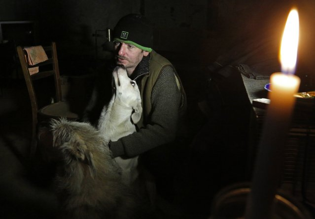 In this photo taken on Monday, October 27, 2014, Vladimir Tumanov, whose home was destroyed in late August, hides from shelling with his dogs in the basement under a hospital not far from Donetsk airport in the town of Donetsk, eastern Ukraine. Donetsk, which has lost about 400,000 of its 1 million pre-war population, is bracing to a winter ahead. (Photo by Dmitry Lovetsky/AP Photo)
