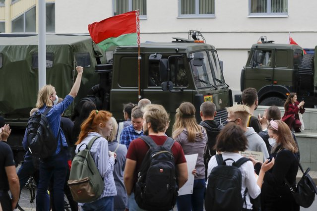 Belarusian school teachers and Belarusian opposition supporters gather on the opposite side of parked police vehicles with attached Belarusian State flag during a rally in the center of Minsk, Belarus, Tuesday, August 25, 2020. (Photo by Sergei Grits/AP Photo)