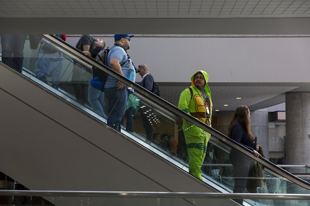 A man dressed as a Teenage Mutant Ninja Turtle rides the escalator at the New York Comic Con in Manhattan, New York, October 8, 2015. (Photo by Andrew Kelly/Reuters)