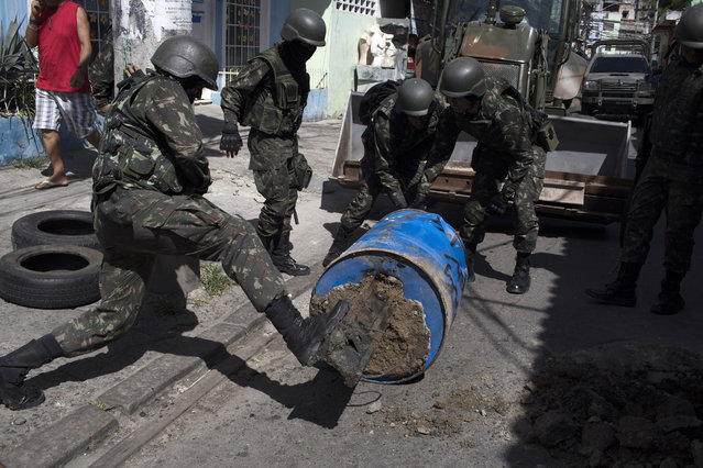 Soldiers remove a barricade during a surprise operation in Jacarezinho slum in Rio de Janeiro, Brazil, Thursday, January 18, 2018. (Photo by Leo Correa/AP Photo)