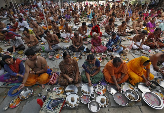 "Hindus perform prayers on the holy day of ""Mahalaya"" in Ahmedabad, India, October 12, 2015. (Photo by Amit Dave/Reuters)"