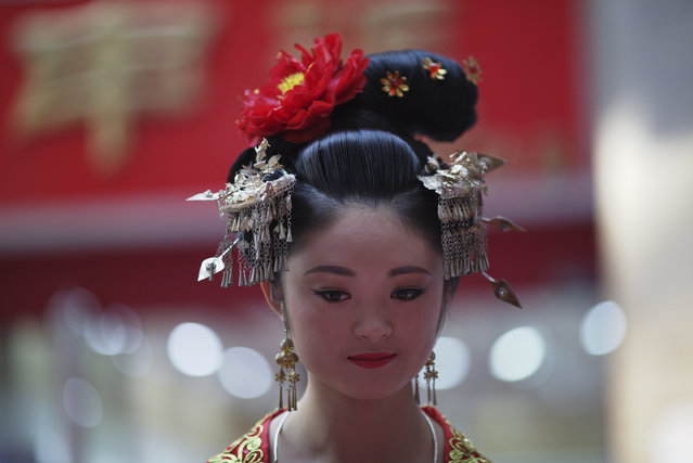 A Chinese model in traditional costumes promotes a photography service at a shopping mall in Yinchuan in northwestern China's Ningxia Hui autonomous region on Sunday, October 11, 2015. China's leaders have sought to reassure the world that China's economy will continue to expand, despite signs that the country's economic growth appears to be slowing. (Photo by Ng Han Guan/AP Photo)