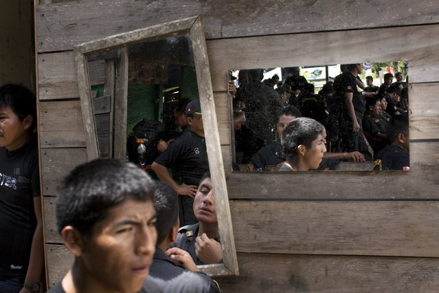 In this November 12, 2014 photo, policemen wait to be airlifted back to their main base, after taking part in an operation to eradicate illegal gold mining camps in the area known as La Pampa, in Peru's Madre de Dios region. (Photo by Rodrigo Abd/AP Photo)