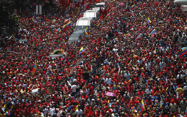 The coffin of Venezuela's late President Hugo Chavez is driven through the streets of Caracas after leaving the military hospital where he died of cancer, in Caracas March 6, 2013. Chavez died on Tuesday of cancer, and authorities have not yet said where he will be buried after his state funeral on Friday. (Photo by Jorge Dan Lopez/Reuters)