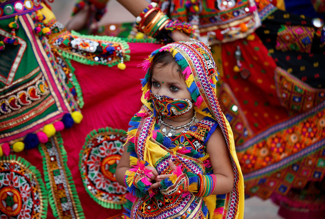 A girl in traditional costume wearing a mask waits to perform in a rehearsal for Garba, a folk dance, ahead of Navratri, a festival during which devotees worship the Hindu goddess Durga and youths dance in traditional costumes, amidst the COVID-19 outbreak, in Ahmedabad, India, September 18, 2020. (Photo by Amit Dave/Reuters)