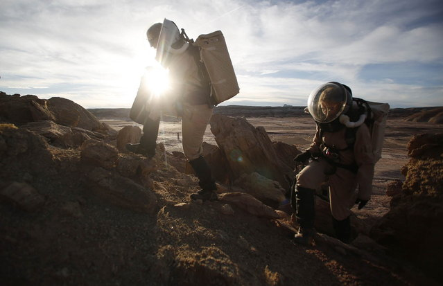 Melissa Battler (L), a geologist and commander of the Crew 125 EuroMoonMars B mission, and Csilla Orgel, a geologist, climb a rock formation to collect geologic samples for study at the Mars Desert Research Station (MDRS) in the Utah desert March 2, 2013. The MDRS aims to investigate the feasibility of a human exploration of Mars and uses the Utah desert's Mars-like terrain to simulate working conditions on the red planet. Scientists, students and enthusiasts work together developing field tactics and studying the terrain. All outdoor exploration is done wearing simulated spacesuits and carrying air supply packs and crews live together in a small communication base with limited amounts of electricity, food, oxygen and water. Everything needed to survive must be produced, fixed and replaced on site. (Photo by Jim Urquhart/Reuters)