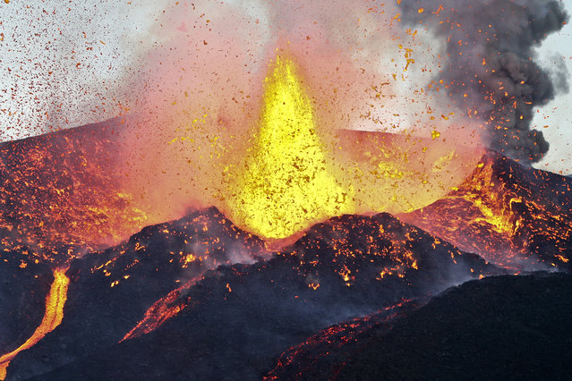 Lava and clouds of smoke and gases are emitted from a volcano on the island of Fogo, near Cha das Caldeiras, Cape Verde, 28 November 2014. The seven sources of lava of the volcanic eruption at Fogo Island that started to flow 23 November 2014 united on 28 November 2014 into one lava flow a kilometer wide. (Photo by Joao Relvas/EPA)
