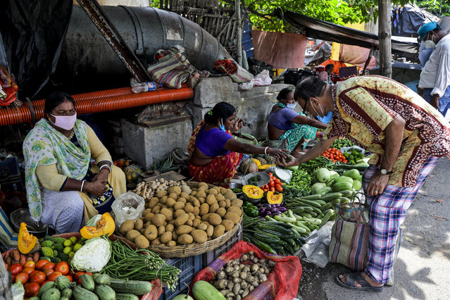 Vendors wearing face masks as a precaution against the coronavirus sell vegetables at roadside stalls in Kolkata, India, Sunday, Aug. 2, 2020. India is the third hardest-hit country by the COVID-19 pandemic in the world after the United States and Brazil. (Photo by Bikas Das/AP Photo)
