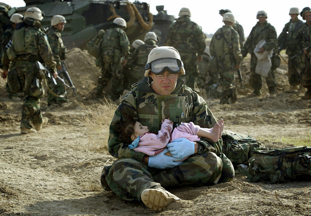 U.S. Navy Hospital Corpsman HM1 Richard Barnett, assigned to the 1st Marine Division, holds an Iraqi child in central Iraq, on March 29, 2003. Confused front line crossfire ripped apart an Iraqi family after local soldiers appeared to force civilians towards positions held by U.S. Marines. (Photo by Damir Sagolj/Reuters/The Atlantic)
