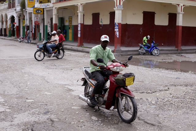 Residents drive motorbikes along a street ahead of Hurricane Matthew in Les Cayes, Haiti, October 2, 2016. (Photo by Andres Martinez Casares/Reuters)