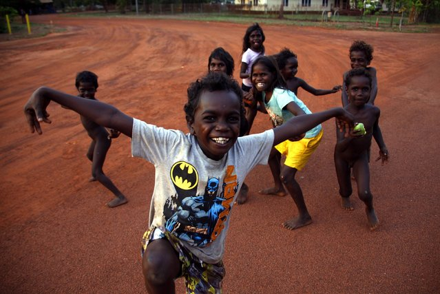 Australian Aboriginal children play on the dirt road that is the main street in the community of Ramingining in East Arnhem Land November 24, 2014. (Photo by David Gray/Reuters)