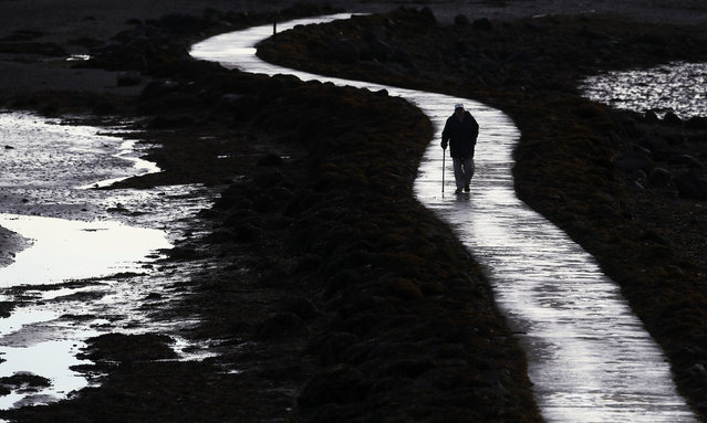 A man walks along a pathway on the shores in County Down, Strangford Lough, Northern Ireland on October 16, 2020t. (Photo by Brian Lawless/PA Images via Getty Images)