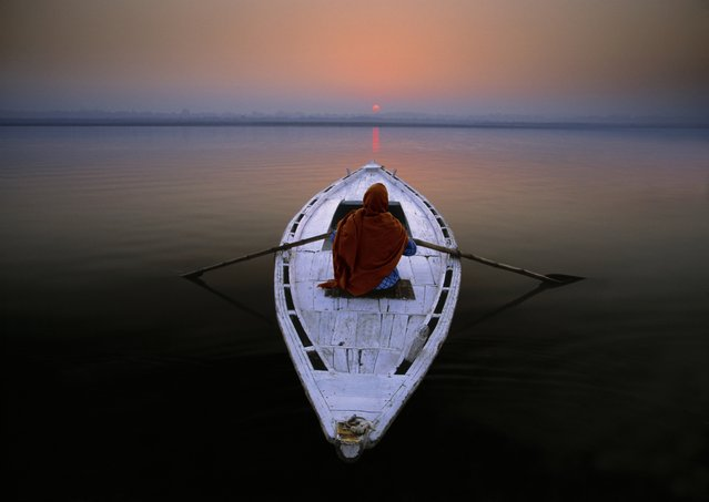 "Spiritual Journey. ""The waters of the Ganges have long been regarded as purifying and sacred among the Hindu religion, due largely to the fact that the river originates high in the nearby Himalayas. In this photograph, a pilgrim sets out upon the Ganges as the sun rises above the distant shore"". (Photo by Art Wolfe/The Guardian)"