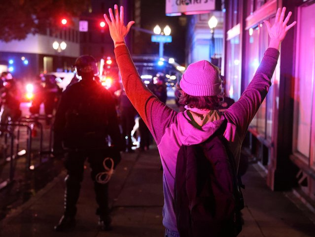 A demonstrator holds up hands in front of police during a protest the day after Election Day in Portland, Oregon, U.S., November 4, 2020. (Photo by Goran Tomasevic/Reuters)