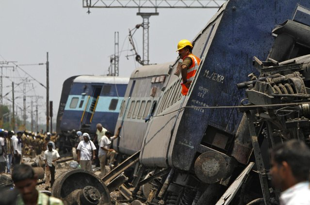 A rescue worker stands on a derailed coach at the site of a train accident near Arakkonam in the southern Indian state of Tamil Nadu April 10, 2013. One person was killed and dozens were injured after a passenger train derailed in Tamil Nadu, local media reported on Wednesday. (Photo by Babu/Reuters)