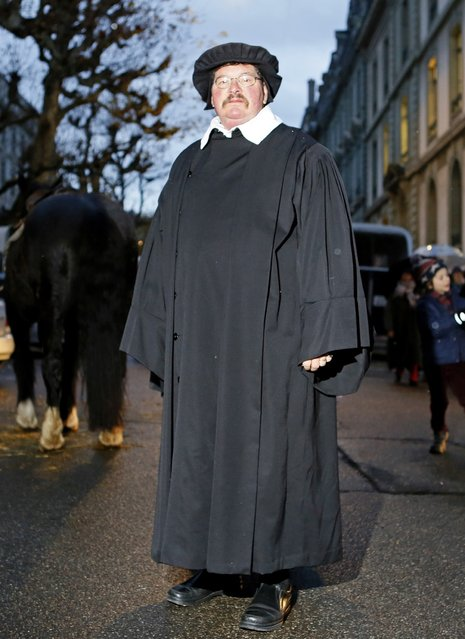 A member of Compagnie 1602 playing the role of a pastor poses before a procession in Geneva December 14, 2014. (Photo by Pierre Albouy/Reuters)