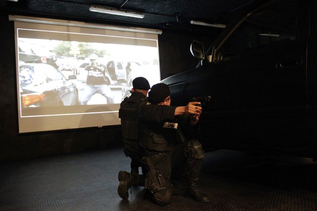 Members of the Fuerza Civil (Civil Force) police unit take part in a gunfight simulation during a media presentation to show the police model that the federal government wants for the rest of the country, at the police academy in Monterrey December 17, 2014. (Photo by Daniel Becerril/Reuters)