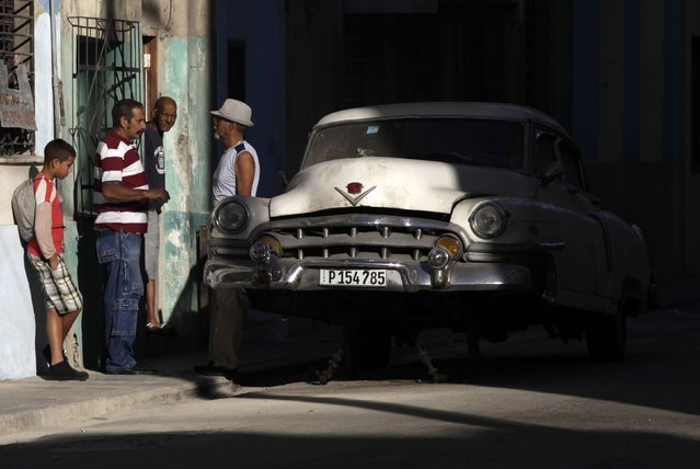 Cubans talk near a broken car in Havana December 19, 2014. With Washington agreeing to restore full diplomatic ties that were cut in the early 1960s, Cuba's communist government may not be able to blame its old Cold War nemesis so readily. Cuba has repeatedly sought to dispel the idea that it secretly wanted the embargo in place, saying if the Americans believed that they should challenge Cuba by lifting it. (Photo by Enrique De La Osa/Reuters)
