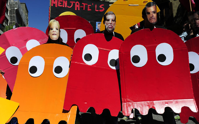 Demonstrators dressed up as characters of the video game Pac-Man and wearing masks of Spanish Prime Minister Mariano Rajoy (C) and German Chancellor Angela Merkel (L), take part a Labour Day march against the Spanish government's austerity policies in the centre of Barcelona on May 1, 2013. Tens of thousands protested across the globe for May Day to press for workers' rights amid tough economic times and to back an array of other causes. (Photo by Josep Lago/AFP Photo)