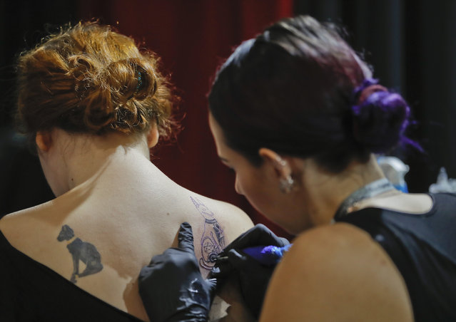 A woman gets a tattoo during the International Tattoo Convention Bucharest 2016 in Bucharest, Romania, Sunday, October 16, 2016. (Photo by Vadim Ghirda/AP Photo)