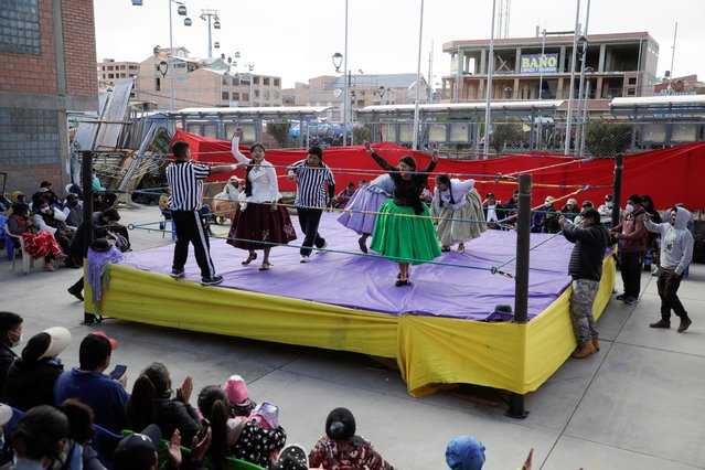 The Fighting Cholitas are a group of female wrestlers who perform in El Alto, Bolivia. Tickets to the exhibitions cost $1. Like the general population of El Alto, which consists almost entirely of Aymara and Quechua residents, the Cholitas are indigenous. They wear braided hair, bowler hats and multilayered skirts in the ring. Here: a view shows the cholitas wrestlers during their return to the ring after the coronavirus disease (COVID-19) restrictions, in El Alto outskirts of La Paz, November 29, 2020. (Photo by David Mercado/Reuters)