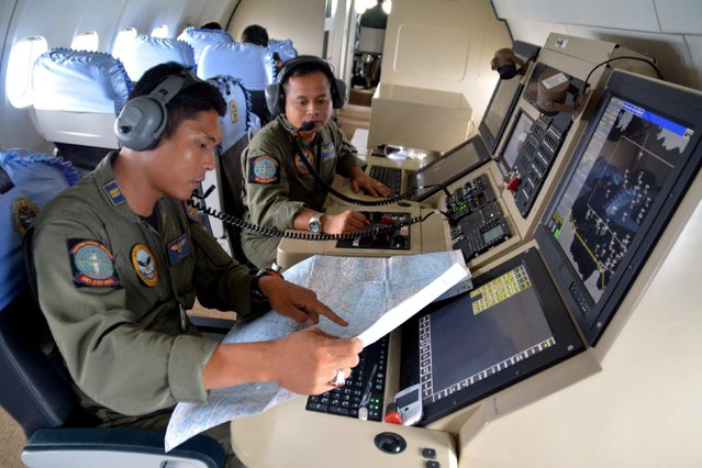 Two members of the Indonesian Navy's Tactical Commanding Operator (TACCO) help with the search for AirAsia flight QZ 8501 on board a CN235 aircraft over Karimun Java, in the Java Sea December 28, 2014 in this photo taken by Antara Foto. (Photo by Eric Ireng/Reuters/Antara Foto)