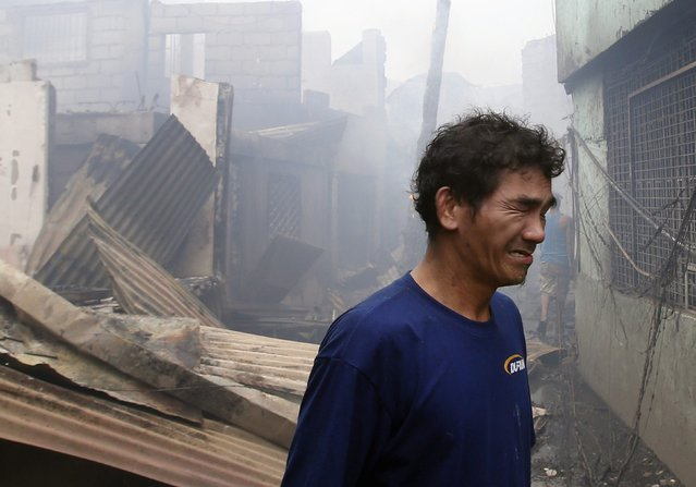 A man weeps outside his house gutted by a fire, at a slum colony in Quezon city, Metro Manila January 1, 2015. (Photo by Erik De Castro/Reuters)
