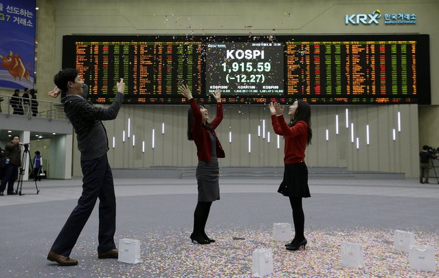 Staff members of the Korea Exchange applaud as they throw confetti for the media during the year's market closing ceremony near a screen showing the Korea Composite Stock Price Index (KOSPI) at the Korea Exchange in Seoul, South Korea, Tuesday, December 30, 2014. The Korea Composite Stock Price Index closed the year's last trading at 1,915.59. (Photo by Ahn Young-joon/AP Photo)