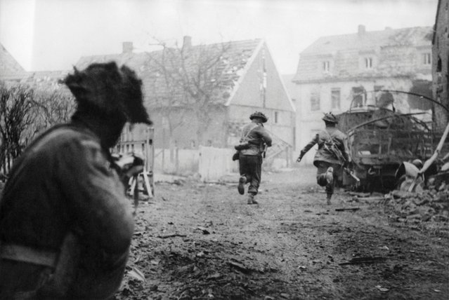Picture released on April 12, 1945 of British soldiers of the 2nd Armored Division launching an offensive through the village of Westphalia, near Stadtlohn, during the Second World War. (Photo by AFP Photo)