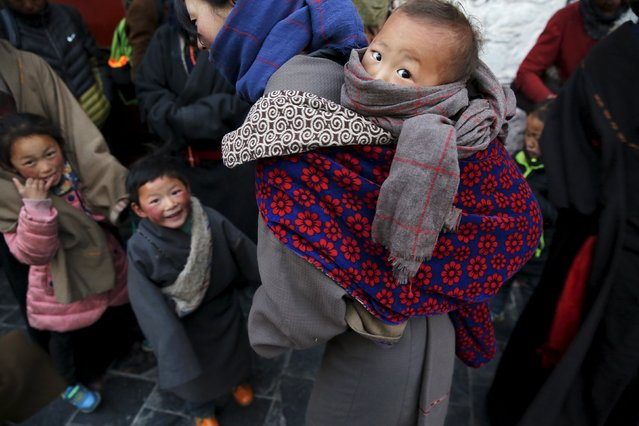 Tibetan pilgrims and their children wait to enter the Jokhang Temple in central Lhasa, Tibet Autonomous Region, China early November 20, 2015. (Photo by Damir Sagolj/Reuters)