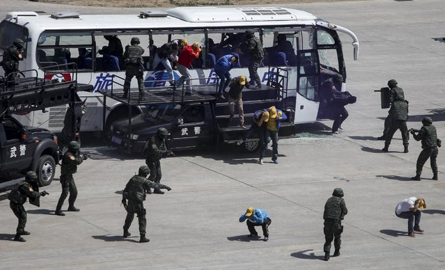 Members of the Snow Leopard Commando Unit rescue hostages from a bus which was hijacked by mock terrorists as they participate in an anti-terrorist drill in Beijing, in this May 29, 2014 file picture. (Photo by Reuters/China Daily)