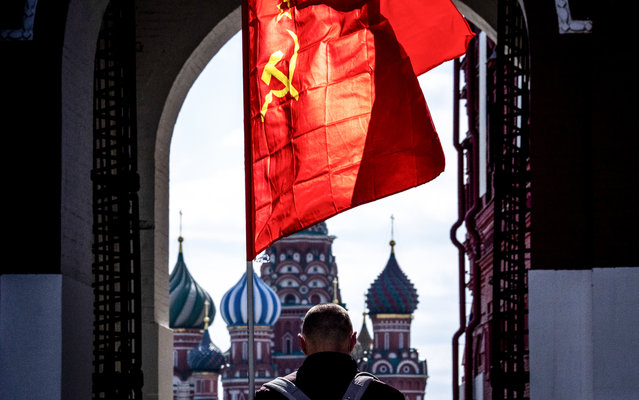 A Russian Communist party supporter carries a red flag as he walks along Red Square in Moscow on May 1, 2020. The Labour Day celebrations were cancelled due to pandemic threat of Covid-19. (Photo by Yuri Kadobnov/AFP Photo)