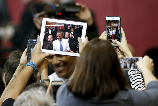 Members of the crowd takes photographs of President Barack Obama after he gave a speech about housing and home ownership as he announces a cut in mortgage insurance premiums on Federal Housing Administration loans, a move aimed at attracting new homebuyers, Thursday, January 8, 2015, at Central High School in Phoenix. (Photo by Ross D. Franklin/AP Photo)