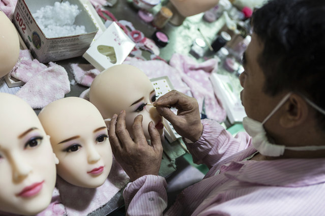 A worker paints make-up on dolls' faces in s*x dolls factory in Dongguan, Guandong Province, China, 24 April 2018. (Photo by Aleksandar Plavevski/EPA/EFE)