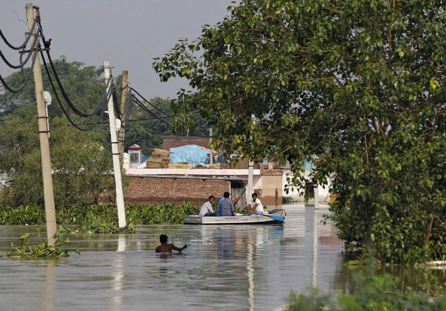 Residents use a boat to secure their belongings from a flooded colony after heavy monsoon rains caused the rise in waters of Yamuna river in New Delhi June 20, 2013. The rains are at least twice as heavy as usual in northwest and central India as the June-September monsoon spreads north, covering the whole country a month faster than normal. (Photo by Anindito Mukherjee/Reuters)