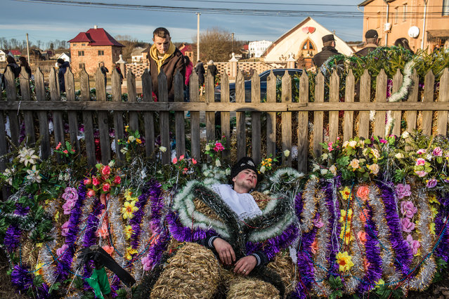 A man rests amongst some decorations as villagers celebrate the winter festival of Malanka on January 14, 2015 in Krasnoilsk, Ukraine. The holiday, which involves dressing in elaborate costumes and going from house to house as a group singing traditional songs, is celebrated on New Year's Day of the Orthodox calendar, a week after Orthodox Christmas. (Photo by Brendan Hoffman/Getty Images)