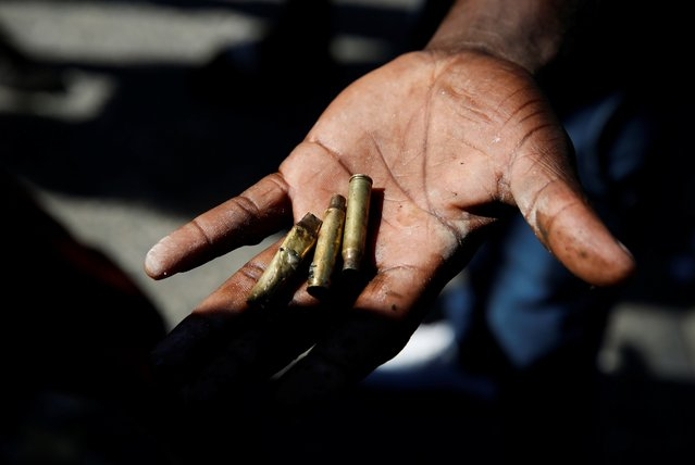 A man shows empty bullet cases during protests against Haiti's President Jovenel Moise, in Port-au-Prince, Haiti on February 7, 2021. (Photo by Jeanty Junior Augustin/Reuters)