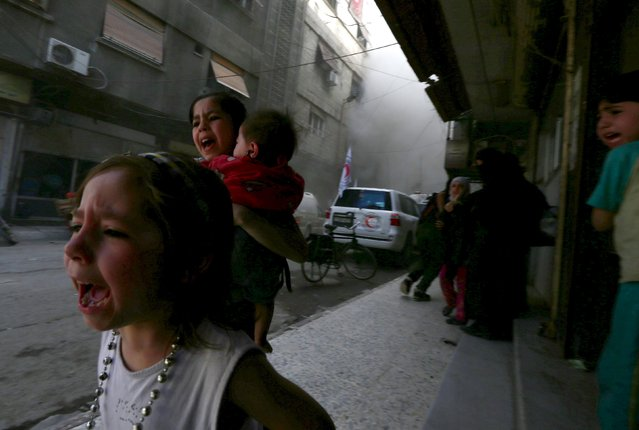 Ghazal, 4, (L) and Judy, 7, carrying 8-month-old Suhair, run away after the shelling of a Red Crescent convoy in Damascus, Syria May 6, 2015. Bassam Khabieh: I was covering the Syrian Arab Red Crescent convoy's visit to the the Douma neighborhood of Damascus, which was carrying medical aid and supplies used to give psychological support to children affected by war. (Photo by Bassam Khabieh/Reuters)