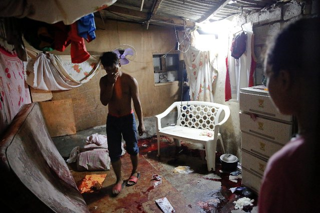 A man walks inside a room in which five people were killed in Manila, Philippines early November 1, 2016. (Photo by Damir Sagolj/Reuters)