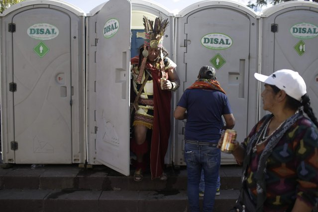 A man dressed a the Inca Emperor Atahualpa leaves of a porta-potty as he holds a beer, in Cuzco, Peru, Saturday, June 23, 2018. June is full of festivities throughout the region of Cuzco, culminating on June 24 with the Inti Raymi, the Festival of the Sun. (Photo by Martin Mejia/AP Photo)