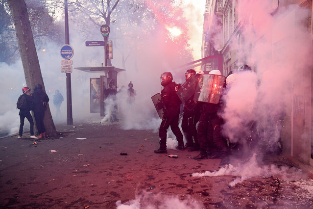 """French riot police officers takes cover during a protest against the """"global security"""" draft law, which Article 24 would criminalise the publication of images of on-duty police officers with the intent of harming their """"physical or psychological integrity"""", in Paris, on November 28, 2020. Dozens of rallies are planned on November 28 against a new French law that would restrict sharing images of police, only days after the country was shaken by footage showing officers beating and racially abusing a black man. (Photo by Alain Jocard/AFP Photo)"""