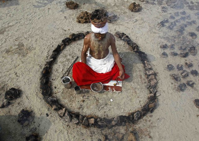 "A Sadhu or a Hindu holy man offers prayers while sitting inside a circle of burning ""Upale"" (or dried cow dung cakes) on the occasion to mark the Basant or spring festival, on the banks of river Ganga in the northern Indian city of Allahabad January 24, 2015. Basant is celebrated mainly in the northern Indian states marking the start of the spring season. (Photo by Jitendra Prakash/Reuters)"