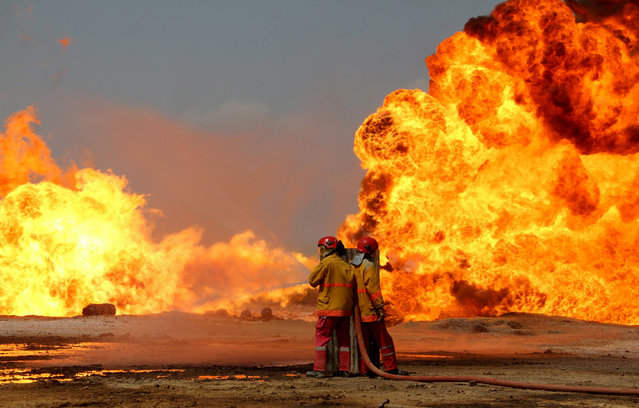 Iraqi firefighters try to stop the fire of burning oil wells in Kirkuk, northern Iraq, 02 June 2016. Two Khabbaz oil field wells in Kirkuk Province, northern Iraq, exploded by suspected insurgents, a security official said. (Photo by EPA/Stringer)
