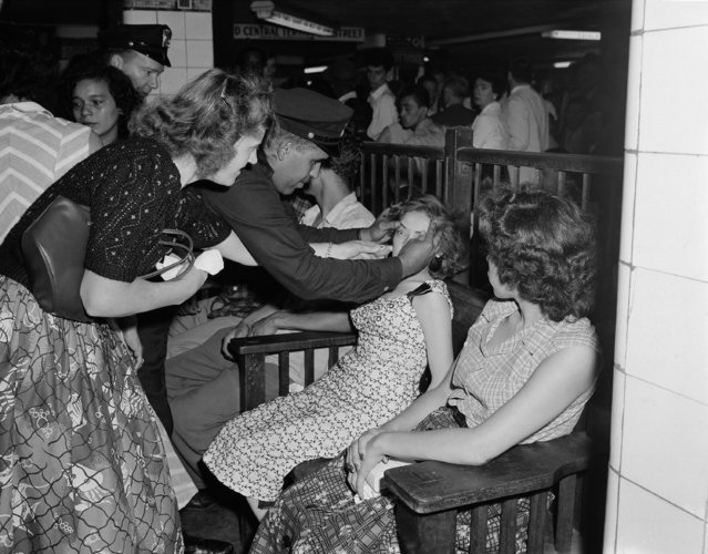 Juana Otero, a victim of heat exhaustion in the abnormally packed Grand Central subway station in New York, gets assistance from transit policeman Arthur Dixon as other victims rest in a corner of the station, July 16, 1956. (Photo by Jacob Harris/AP Photo)