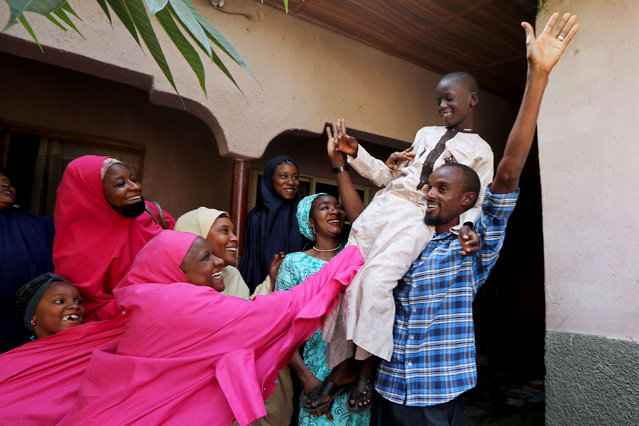 Muhammed Bello, a rescued student, is carried by his father as his relatives celebrate after he retuned home in Kankara, Nigeria, December 19, 2020. (Photo by Afolabi Sotunde/Reuters)