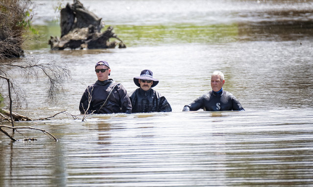 "Police officers wade through water as they search for missing woman Ju Zhang at Darebin Creek in Melbourne, Monday, February 22, 2021. Missing Persons Squad detectives have returned to Heidelberg West as part of the ongoing search for missing Epping woman Ju ""Kelly"" Zhang. (Photo by Luis Ascui/AAP Image)"