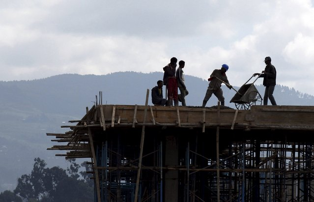 "Construction workers work on the roof of a new building at the Mercato market in Addis Ababa September 11, 2015. Addis Ababa's ""Mercato"" – Italian for ""market"" – is reputedly the biggest open-air market in Africa, lying in the west of the capital. Supermarkets have sprouted across the city as the metropolis has expanded with Ethiopia's booming economy, but Mercato remains a popular destination for shoppers seeking clothing, electronics and a huge range of other items. (Photo by Tiksa Negeri/Reuters)"