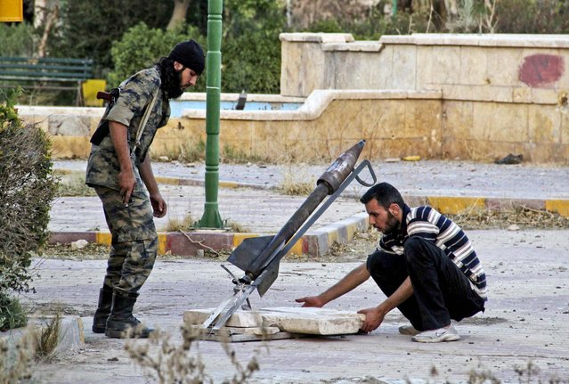 Free Syrian Army fighters set up a homemade rocket for launch in Deir al-Zor, on July 21, 2013. (Photo by Karam Jamal/Reuters)