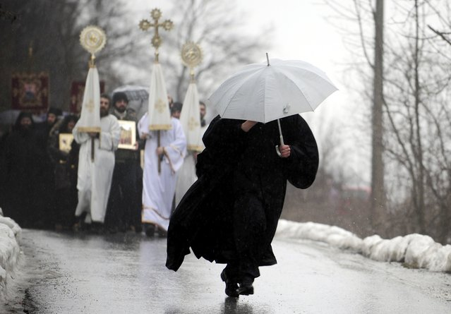 A priest, carrying an umbrella, heads a procession during an Epiphany day celebration in Bitushe village, about 150km (93 miles) west from the capital Skopje, January 19, 2015. Bitushe practises a different Epiphany tradition. (Photo by Ognen Teolovski/Reuters)